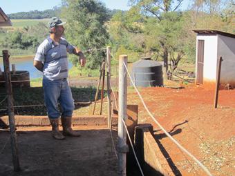 Gedson Vargas, no estábulo onde recolhe excrementos bovinos que, com água, escorrem por um canal até o biodigestor cinza que se vê atrás. As águas da lagoa estão menos contaminadas.