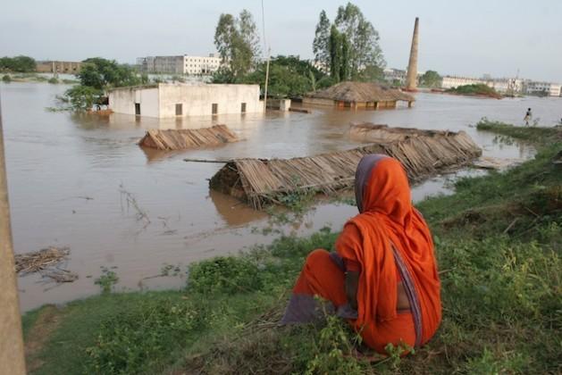 Uma mulher observa impotente como a água inunda sua cabana com teto de palha e todas as suas posses nos arredores da cidade de Bhubaneswar, no Estado de Odisha, na Índia, em 2008. Foto: Manipadma Jena/IPS