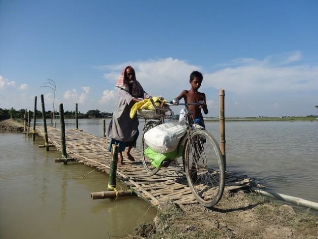 As devastadoras inundações, que em 2014 causaram estragos no Estado de Assam, na Índia, levaram o governo a construir pontes de bambu. Este homem e este menino vão de uma aldeia a outra de barco e cruzam as pontes a pé. Foto: Priyanka Borpujari/IPS