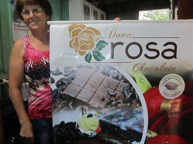 Rosalina Brighanti, conhecida como Dona Rosa, em sua cozinha, onde prepara doces, com o cartaz dos chocolates orgânicos, feitos sob padrões especiais da família, reconhecidos por consumidores e comerciantes no Brasil e no exterior. Foto: Mario Osava/ IPS