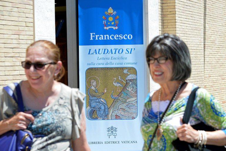 Turistas no Vaticano passam por cartaz sobre a encíclica papal que tratou do clima