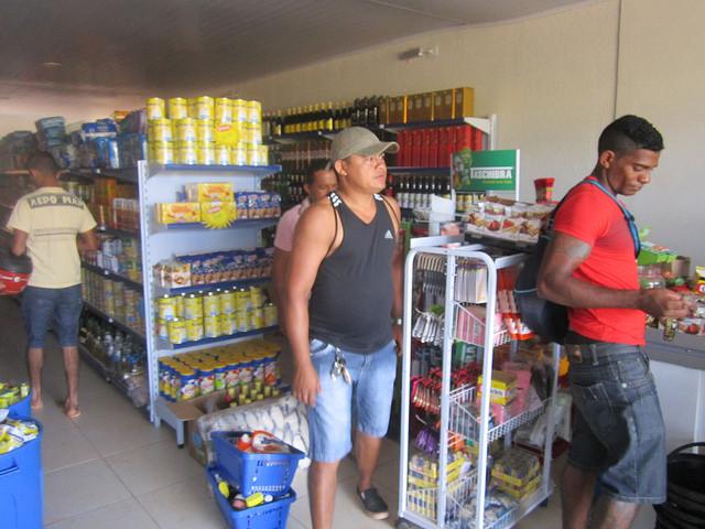 Francisco Assis Cardoso, no centro, de camiseta escura, em seu novo comércio de alimentos. Este jovem empreendedor instalou um supermercado e uma farmácia em Jatobá, o novo bairro de Altamira em que toda sua família foi reassentada devido à construção da central de Belo Monte, na Amazônia brasileira. Foto: Mario Osava/IPS