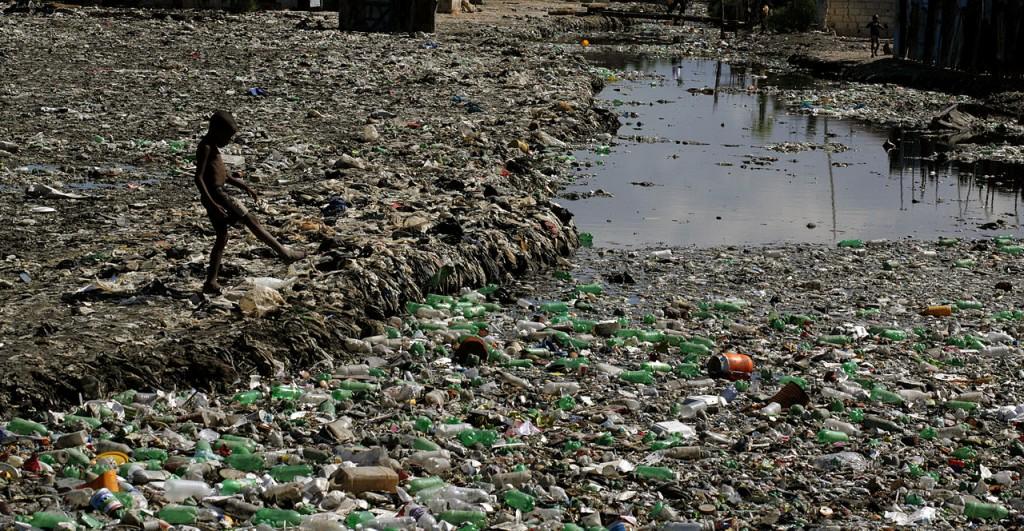 Menino passeia á margem de um rio bloqueado pela quantidade de lixo. Foto: Wikicommons/Thomas Black57 (CC)