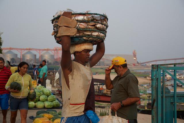 Pescador carrega sua captura do dia no mercado da cidade de Santarém, na praia fluvial onde agora dominam os silos do porto, na confluência dos rios Tajapós e Amazonas, no Estado do Pará, norte do Brasil. Foto: Gonzalo Gaudenzi/IPS