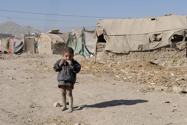 Um menino refugiado afegão come um doce em frente à barraca de campanha que sua família ocupa. Foto: DVIDSHUB/CC-BY-2.0