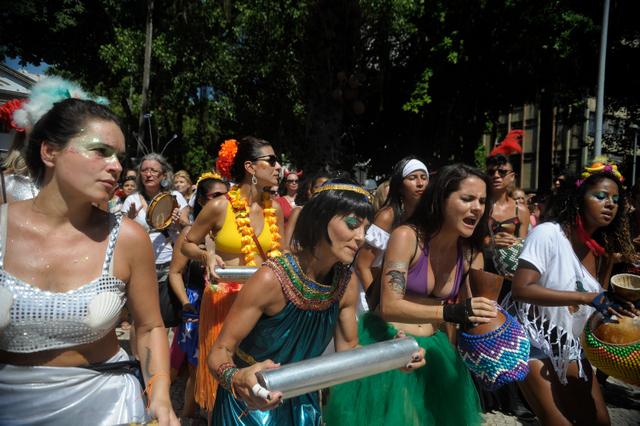 Integrantes de um bloco de mulheres dançam portando instrumentos de raízes africanas, em desfile em um bairro do Rio de Janeiro durante o carnaval deste ano, que confirmou o resgate popular da festa. Foto: Tânia Rêgo/Agência Brasil