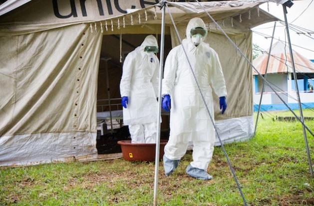 Dois trabalhadores da saúde colocam os pés em um recipiente de água com hipoclorito de sódio, à saída de uma barraca de campanha em isolamento durante uma simulação de atendimento a pacientes com ebola, no hospital de Biankouman, na Costa do Marfim, em agosto de 2014. Foto: Marc-André Boisvert/IPS