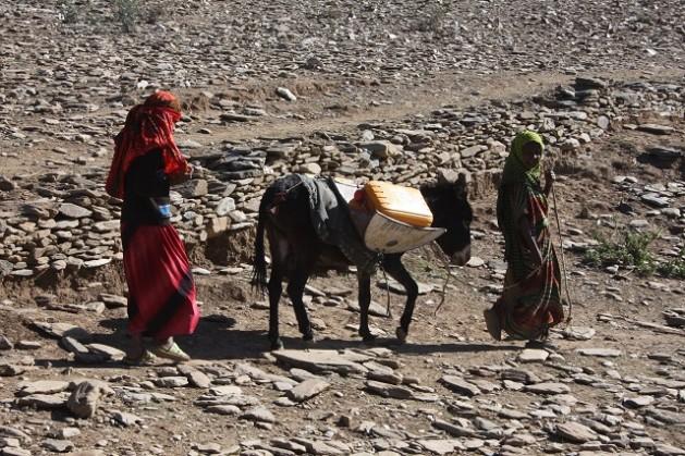 Jovens conduzem um burro que carrega água na Etiópia. Foto: James Jeffrey/IPS
