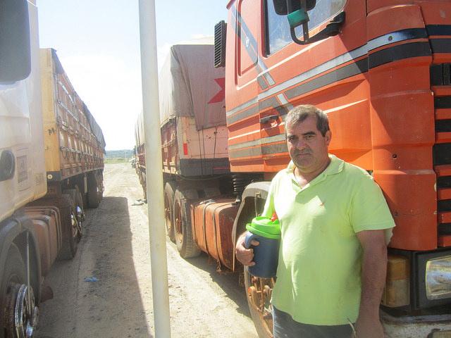 """Martin Echauri concorda com outros caminhoneiros que transportam soja para o Complexo Agroindustrial Angostura SA (Caiasa) quanto a essa processadora de soja ser """"uma benção"""", pela rapidez do processo de descarga dos 500 veículos de grande tonelagem, que chegam às suas instalações, em Angostura, no parque industrial de Villeta, no Paraguai. Echauri se distrai enquanto espera compartilhando com outros caminhoneiros o mate, bebida popular nos países do Cone Sul americano. Foto: Mario Osava/IPS"""