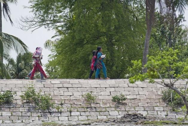 Meninas caminham por um muro de contenção no distrito de Satkhira, em Bangladesh. A altura das barreiras deverá ser elevada para proteger as populações costeiras do aumento das tempestades e dos ciclones. Foto: Rafiqul Islam/IPS