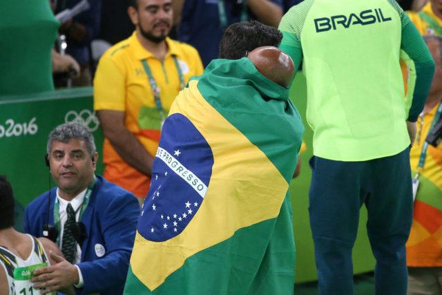 O ginasta Diego Hypolito, envolto pela bandeira do Brasil e abraçado por seu treinador após ganhar a medalha de prata na competição de solo, se tornou outro novo herói olímpico do país, ao conquistar essa medalha já com 30 anos, depois de ter fracassado nos Jogos de 2008 e 2012. Foto: Roberto Castro/Brasil 2016