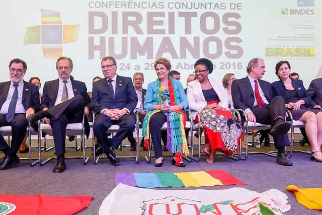 A presidente Dilma Rousseff, sentada ao centro, com uma flor na mão que lhe foi entregue durante a abertura da Conferência Nacional de Direitos Humanos, no dia 27 deste mês, em Brasília. Nos atos da presidente nos últimos dias se repetem os gestos de carinho com tom de despedida. Foto: Roberto Stuckert Filho/PR