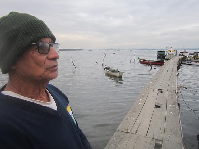 Sérgio Souza dos Santos no cais construído pelos pescadores de Tubiacanga, para entrar na baía de Guanabara, no Rio de Janeiro, porque a sedimentação impede que suas embarcações se aproximem da margem, que há décadas era uma bela praia. Foto: Mario Osava/IPS
