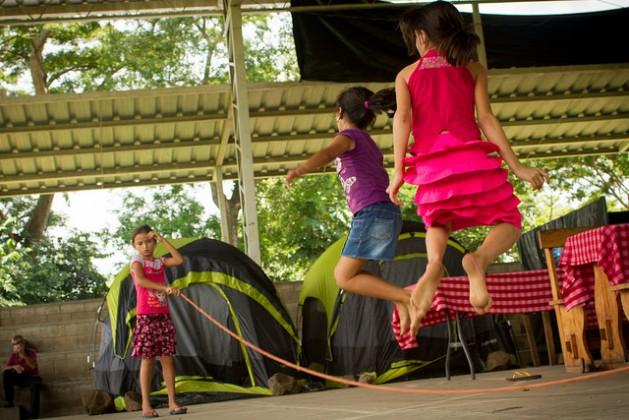 Meninas pulam corda no abrigo onde elas e suas famílias permanecem refugiadas na localidade de Caluco, no ocidente de El Salvador, em uma instalação improvisada em uma quadra de basquetebol. Dezenas de famílias fugiram em massa da vizinha comunidade agrícola de El Castaño devido à violência e às ameaças de gangues. Foto: Edgardo Ayala/IPS