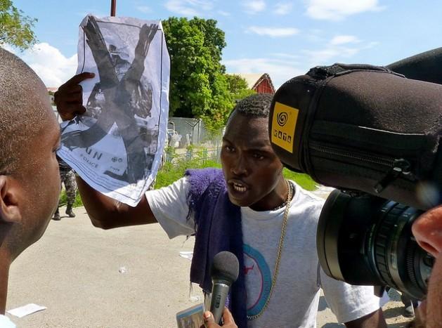 Manifestante segura um cartaz contra a ONU durante um protesto em frente à base da organização em Porto Príncipe, no Haiti. Foto: AnselHerz/IPS