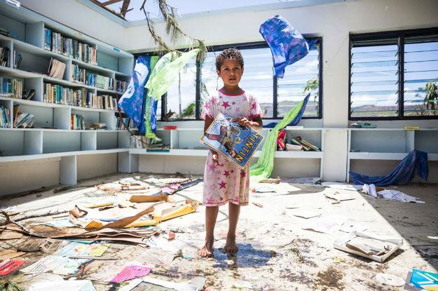 Menina de sete ano em biblioteca destruída na província de Ra, Fiji. Foto: UNICEF/UN011701/Sokhin