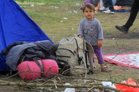 Menino afegão mostra os pertences de sua família em frente a uma barraca de campanha, perto de Röszke, na Hungria. Foto: Zsolt Balla/© Alto Comissariado para os Refugiados