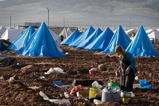 Mulher prepara refeição no acampamento para refugiados internos Bab Al Salame, em Alepo, na Síria, perto da fronteira com a Turquia, em janeiro de 2014. Foto: Ocha/ONU